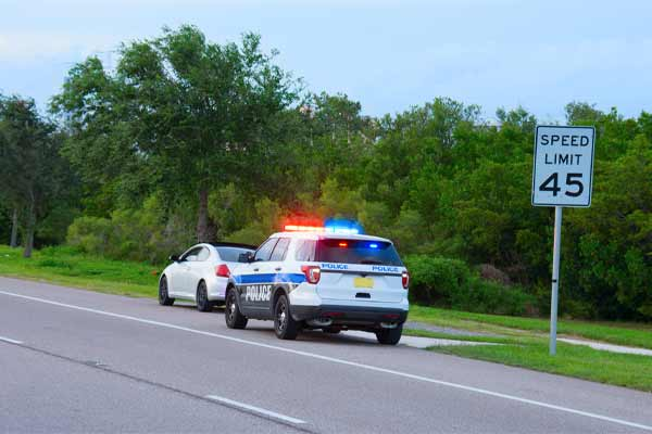 A driver pulled over to the side of the road by a police vehicle.